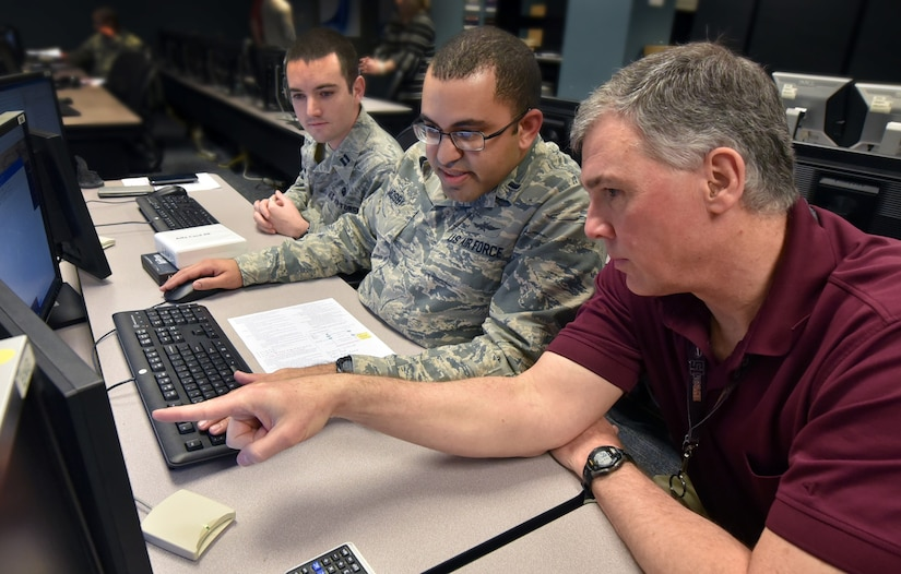 Air Force Institute of Technology students listen as professor (right) explains hacking technique during class at Wright-Patterson Air Force Base, Ohio,