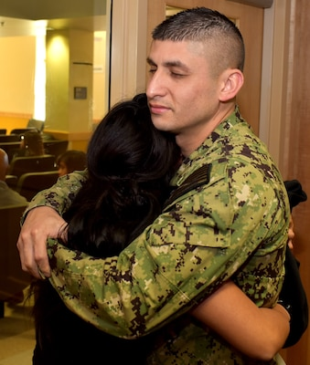 Petty Officer 1st Class Ivan Aguilar of Pharr, Texas, embraces his sister, Lesley Torres, of Edinburg, Texas, after Torres took the oath of enlistment at the San Antonio Military Entrance Processing Station.  Aguilar is a division leading petty officer assigned to Navy Recruiting Station McAllen, Navy Recruiting District San Antonio and helped enlist his sister into the Navy.  Torres, a 2018 graduate of Edinburg North High School, is the third of three siblings and the first female in her family to serve in the military.