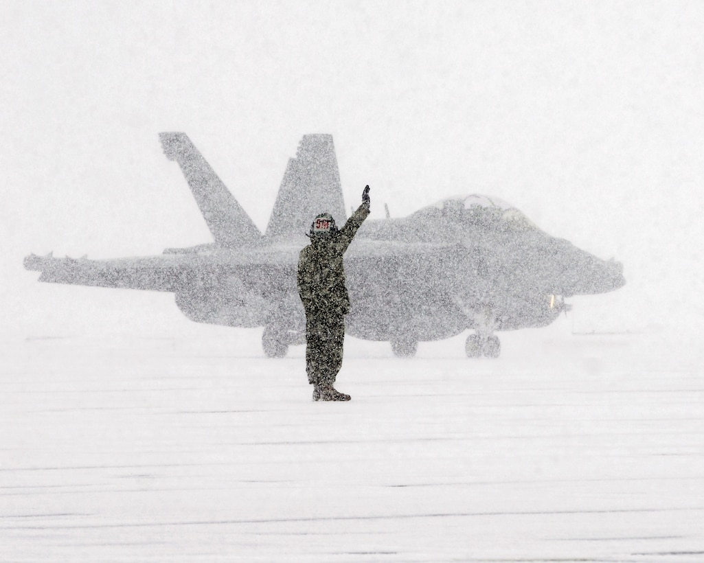 Sailor assigned to Electronic Attack Squadron (VAQ) 132 signals to E/A-18G Growler pilot as he taxis on flight line during snowstorm at Naval Air Facility Misawa, Japan, January 10, 2013 (U.S. Navy/Kenneth G. Takada)