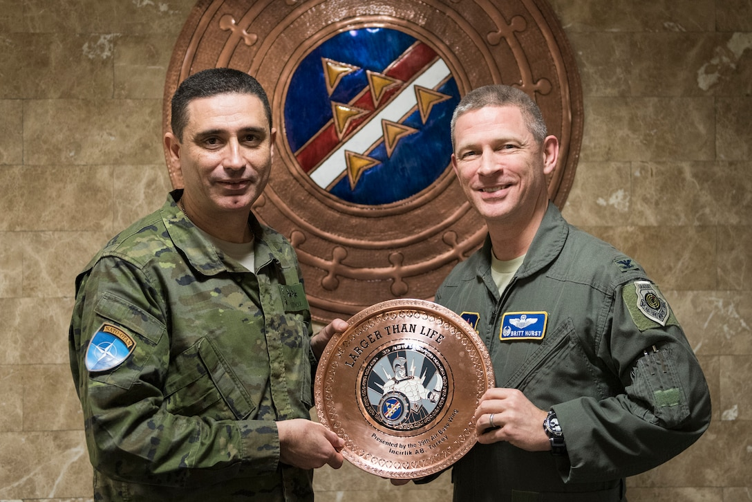 U.S. Air Force Col. Britt Hurst, 39th Air Base Wing commander, and Spanish army Lt. Col. Jose Alberto Munoz Martinez, Spanish Patriot Unit commander, pose during a going-away gift exchange at Incirlik Air Base, Turkey, Jan. 16, 2019.