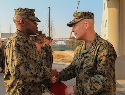 CAMP HUMPHREYS, Republic of Korea – Master Sgt. Olatokunb A. White, U.S. Marine Corps Forces Korea G-6 communications chief, receives the Navy and Marine Corps Commendation Medal from Maj. Gen. Patrick J. Hermesmann, MARFORK commander, here, Jan. 22. White led the communications section of MARFORK and helped set the force for Marine Corps communications in Korea. (Official U.S. Marine Corps photos by Sgt. Nathaniel Hanscom/Released)