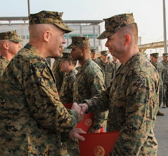 CAMP HUMPHREYS, Republic of Korea – Gunnery Sgt. Roger Reyes, U.S. Marine Corps Forces Korea ammunitions chief, receives a Certificate of Commendation from Maj. Gen. Patrick J. Hermesmann, MARFORK commander, here Jan. 22. Reyes was awarded the CERTCOM for excellence in putting together and leading the Camp Humphreys Chili Cook Off held by MARFORK in conjunction with the Army versus Navy football game. (Official U.S. Marine Corps photos by Sgt. Nathaniel Hanscom/ Released)