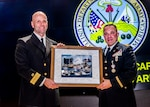 Two military officers stand on stage holding a frame with signatures around the edge and picture of the installation in the middle
