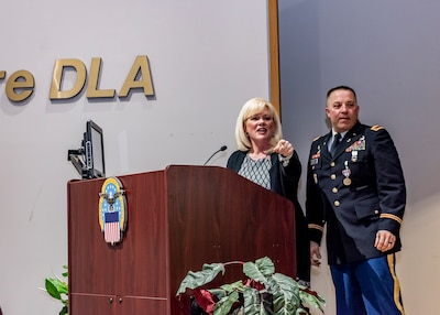 A woman points across the stage standing next to a military man, both behind a podium