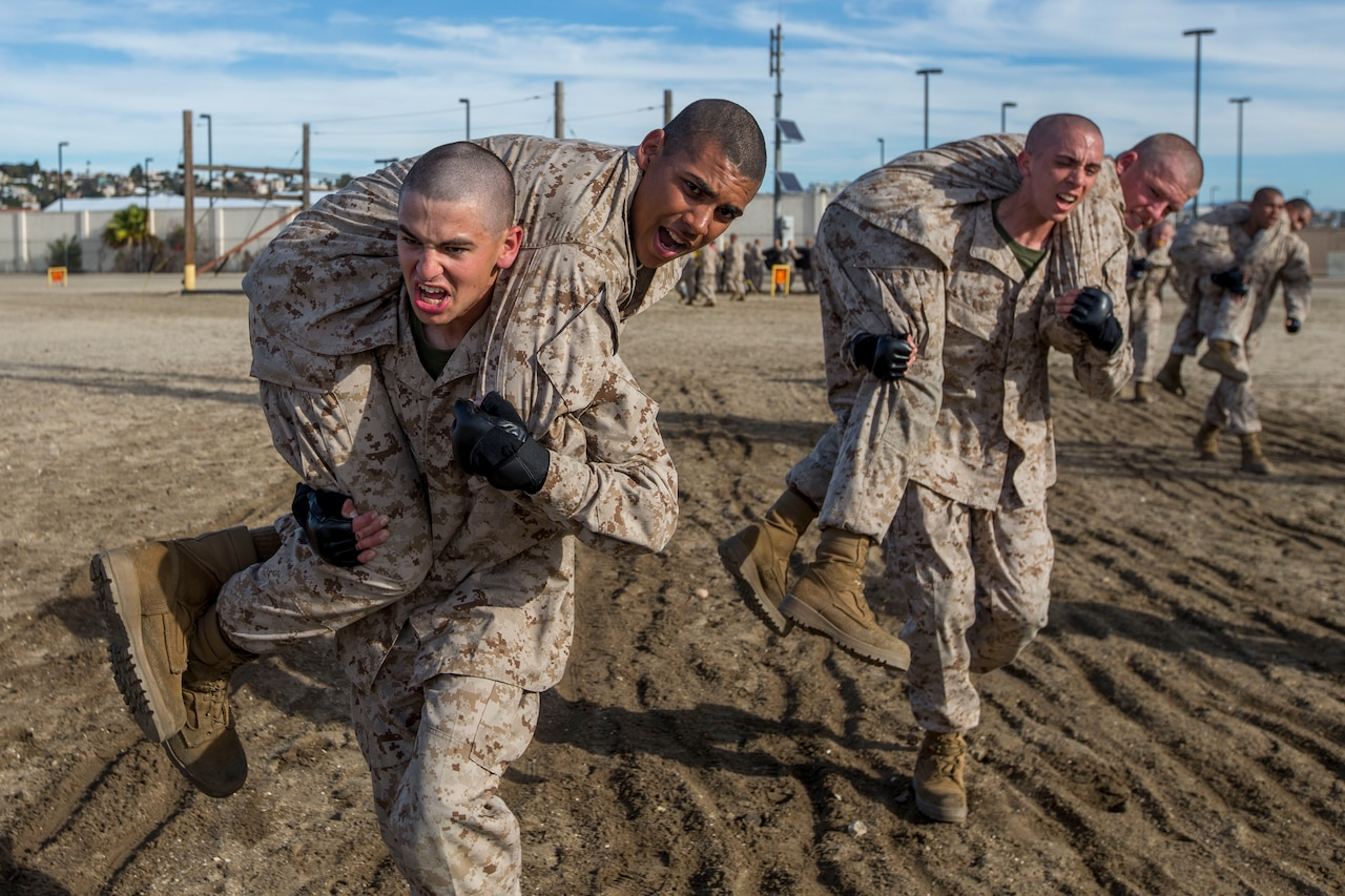 Marine recruits carry each other.