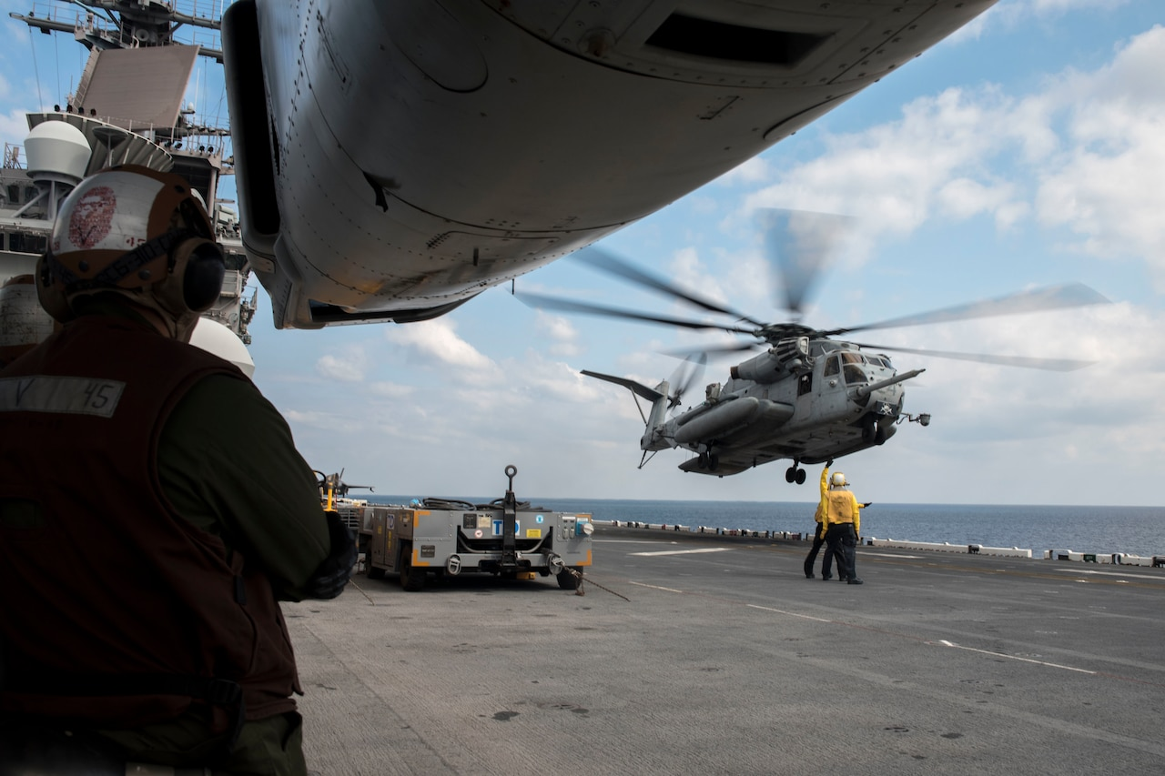 A helicopter hovers over a ship.