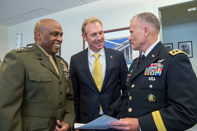 A Marine, a civilian and a soldier stand together in conversation.