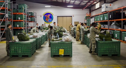 Airmen inspect their issued equipment during a pre-deployment function line exercise Jan. 23, 2019, at Joint Base Charleston, S.C.