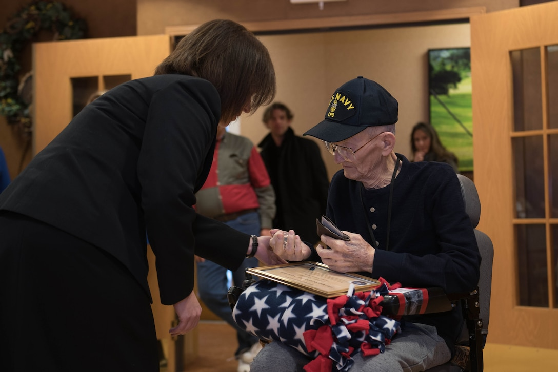 Senior Chief Petty Officer Lisa Vrtiska, U.S. Strategic Command Navy Element senior enlisted leader, presents a pin to Navy veteran Chief Petty Officer Leonard Kulceski during a veteran recognition ceremony at Hillcrest Mable Rose in Papillion, Nebraska, Jan. 18, 2019. Kulceski was named the youngest chief petty officer. (U.S. Air Force photo by Zachary Hada)