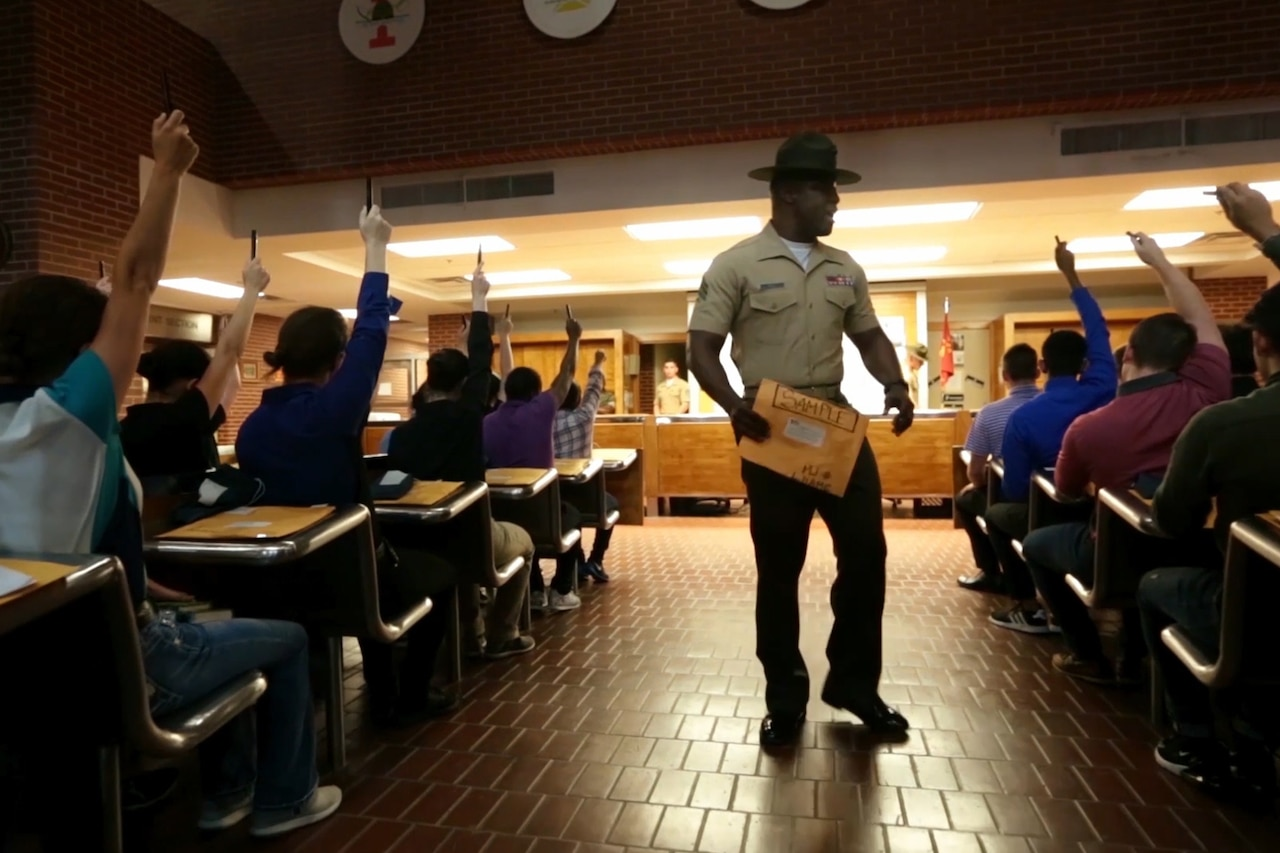 A Marine Corps drill instructor gives instructions to recruits seated at desks and raising their hands.