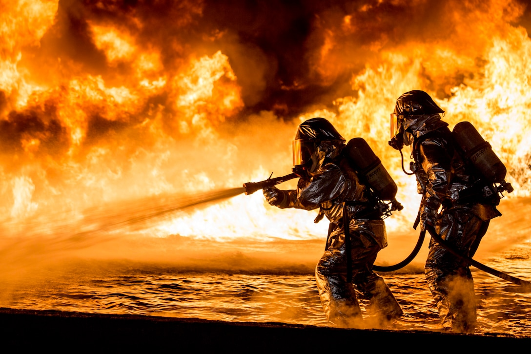 U.S. Marines with Aircraft Rescue and Firefighting use a hand line to extinguish a fuel fire Jan. 25, 2019, during live-burn training at Marine Corps Air Station Futenma, Okinawa, Japan. The training is held monthly to provide ARFF Marines with training scenarios to enhance their readiness to respond to any potential hazards or emergencies on the flight line. ARFF Marines entered the training area and used various hand lines, also known as a fire hose, to control and extinguish the fire.