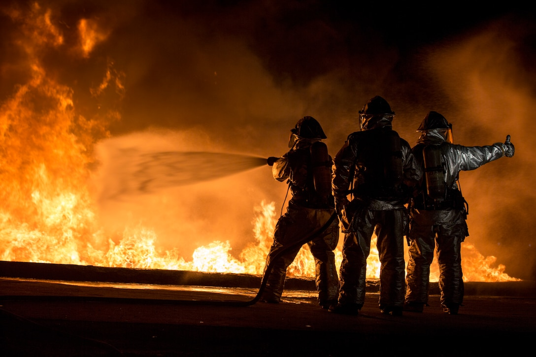 U.S. Marines with Aircraft Rescue and Firefighting use a hand line to extinguish a fuel fire Jan. 24, 2019 during live-burn training on Marine Corps Air Station Futenma, Okinawa, Japan. The training is held monthly to provide ARFF Marines with training scenarios to enhance their readiness to respond to any potential hazards or emergencies on the flight line. ARFF Marines entered the training area and used various hand lines, also known as a fire hose, to control and extinguish the fire.