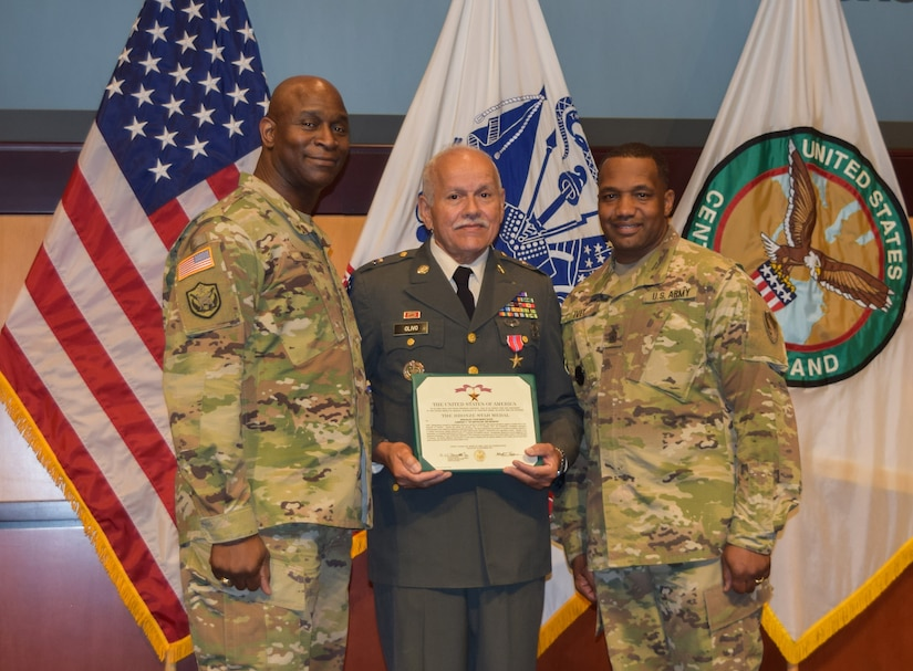 Maj. Gen. Mitchell L. Kilgo, U.S. Central Command's Army element commander, left, and Command Sgt. Maj. Charles Ivey, U.S. Central Command's Army element senior enlisted leader, right, stand with retired Sgt. 1st Class Mario Olivo during a ceremony at U.S. Central Command headquarters, Jan. 22, 2019. Olivo was awarded a Bronze Star medal for service with Charlie Company, 1st Battalion, 52nd Infantry in the Republic of Vietnam from Jan. 1971 until Oct. 1971.