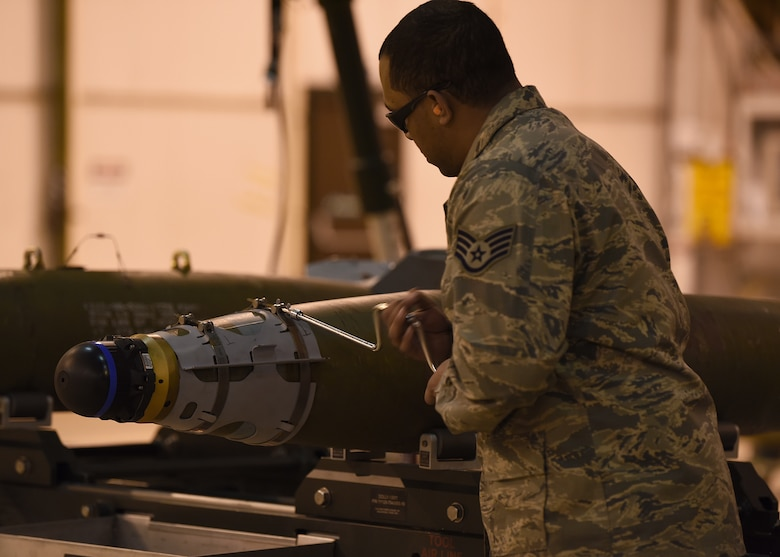 Staff Sgt. Deion Montana-Graham, 48th Munition Squadron conventional maintenance supervisor, uses a speed handle wrench to install the front strakes on an inert ordnance at Royal Air Force Lakenheath, England, Jan. 23, 2019. Practicing for the Air Force Combat Operations Competition provides a training opportunity for noncommissioned officers and Airmen they don't normally get during day-to-day operations. (U.S. Air Force photo by Airman 1st Class Madeline Herzog)