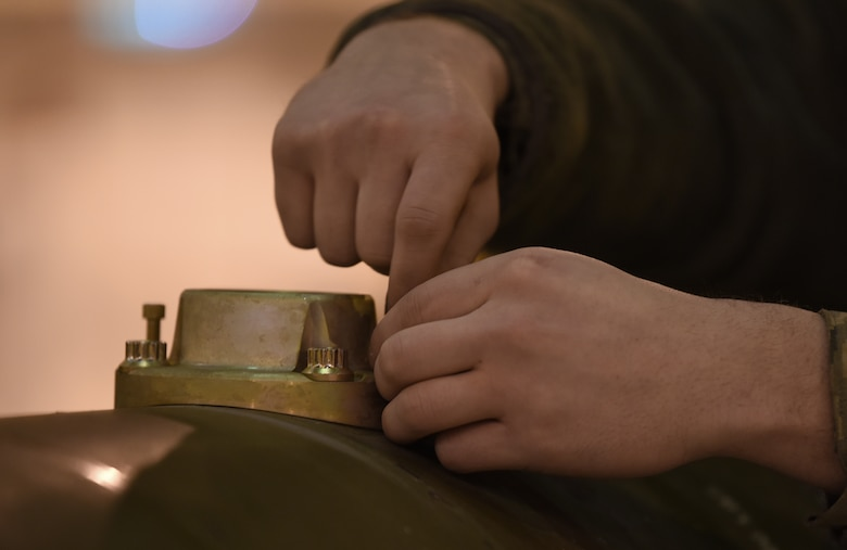 A 48th Munitions Squadron Airman fastens parts together on an inert weapon at Royal Air Force Lakenheath, England, Jan. 23, 2019. MUNS Airmen have been training and preparing for the Air Force Combat Operations Competition scheduled for May at Beale Air Force Base, Calif. (U.S. Air Force photo by Airman 1st Class Madeline Herzog)