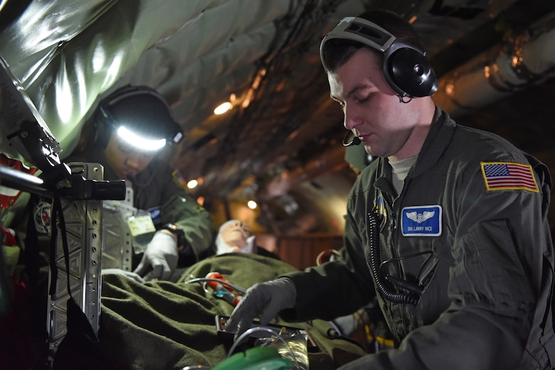 U.S. Air Force Staff Sgt. Yannick Sharras, left, 86th Aeromedical Evacuation Squadron medical technician from Ramstein Air Base, Germany, and U.S. Air Force Senior Airman Larry Nice, 86th AES medical technician, prepare a patient for medical evacuation during training aboard a KC-135 Stratotanker over the skies of Germany, Jan. 23, 2019. During the training, members underwent emergency medical scenarios, including patients suffering worsening health conditions, cardiac emergencies, aircraft decompression and emergency ditching of aircraft. (U.S. Air Force photo by Airman 1st Class Brandon Esau)
