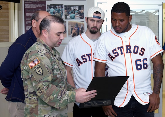 Sgt. 1st Class Daniel Peters (left) describes the mission and capabilities of the U.S. Army Institute of Surgical Research Burn Center Burn Flight Team to Houston Astros pitchers Dean Deetz, Rogelio Armenteros and Astros broadcaster Alex Trevino during their visit to the U.S. Army Institute of Surgical Research Burn Center at Joint Base San Antonio-Fort Sam Houston Jan. 24.