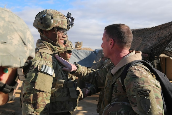 U.S. Army Command Sgt. Maj. William F. Thetford, U.S. Central Command senior enlisted leader, presents coins to U.S. Army Soldiers during a training exercise in Iraq, Jan. 16, 2019. The Soldiers are deployed in support of Operation Inherent Resolve, working by, with and through the Iraqi Security Forces and Coalition partners to defeat ISIS in areas of Iraq and Syria. ( U.S. Army photo by Sgt. Franklin Moore)