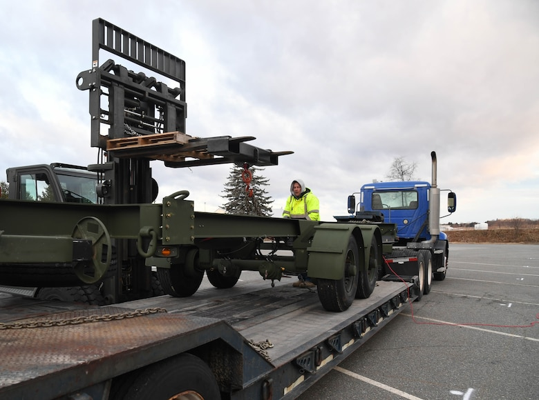 66th Air Base Group Logistics Readiness Squadron employees coordinate the unloading of a testing trailer Jan. 10, 2019, at Hanscom Air Force Base, Mass. Program Executive Office Digital purchased the trailer to test loading and delivery characteristics for the Three Dimensional Expeditionary Long Range Radar, or 3DELRR. (U.S. Air Force photo by Linda LaBonte Britt)