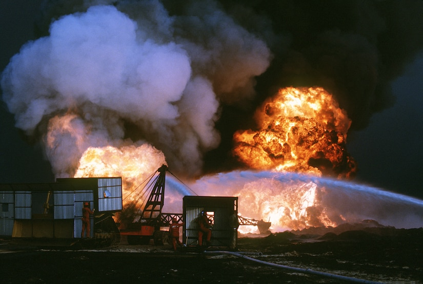 Personnel from Santa Fe Drilling Company and Red Adair Oil Well firefighters battle blaze from burning oil well set afire by Iraqi forces prior to their retreat