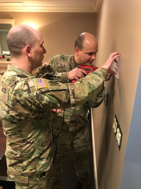 Two male Soldiers drilling into wall