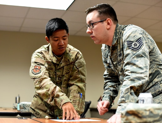 U.S. Air Force Capt. Ric Rebulanan, 17th Training Wing chief of international training, explains to Tech. Sgt. Andrew Lorkrantz, 313th Training Squadron instructor, international training, how to apply the value of the rolled dice into statistics used in a game version of attacking a fictional base during the International Intelligence Applications Officers Course at Goodfellow Air Force Base, Texas, Jan. 11, 2019. The IIAOC course has undergone updating to include more interactive techniques for the students. (U.S. Air Force photo by Senior Airman Seraiah Hines/Released)