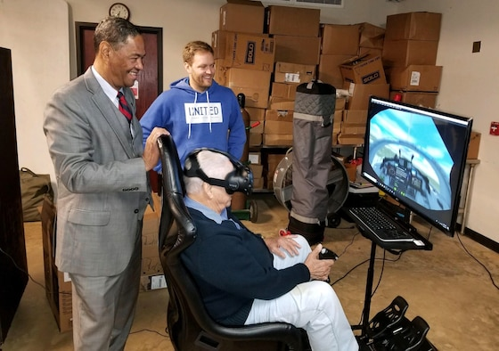Retired Air Force Lt. Col. George Hardy (left), a former Tuskegee Airman, flies the VR flight simulator.