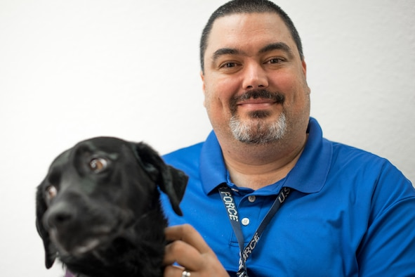 Kevin Waterhouse, along with his service dog Jade, serves as the wing commander's secretary for the 403rd Wing at Keesler Air Force Base, Mississippi. He was in an accident at age 17 that left him paralyzed from the chest down. He didn't let that get him down or stop him from achieving his goals of getting an advanced degree, writing a book, and getting a federal job. (U.S. Air Force photo by Staff Sgt. Shelton Sherrill)
