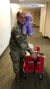 Male Soldier holding toys donated to Ronald McDonald House