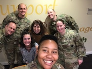 Seven Soldiers - male and female - posing for photo at Ronald McDonald House