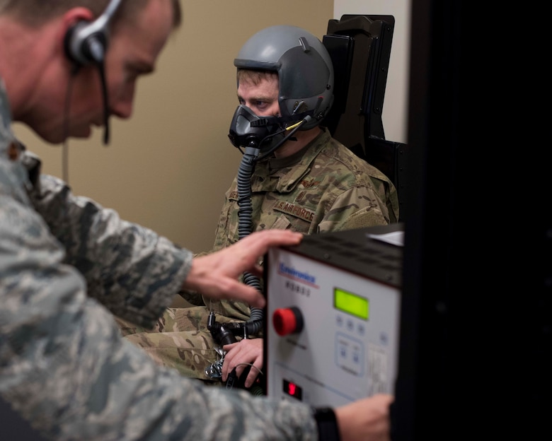 Maj. Zachary Garrett, 49th Medical Group Human Performance flight commander, adjusts the oxygen level during a hypoxia recognition simulation for Tech. Sgt. Jonathan Andrew, 49th MDG Education and Training flight chief, Jan. 11, 2019, on Holloman Air Force Base, N.M. As an aerospace physiologist, Garrett conducts hypoxia recognition and recovery training and studies human factors in the flight environment for 49th Wing aircrew. (U.S. Air Force photo by Staff Sgt. BreeAnn Sachs)