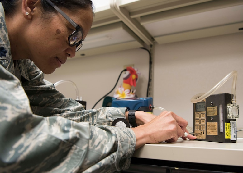Lt. Col. Elisa Hammer, 49th Medical Group Biomedical Engineering flight commander, calibrates an air pump, Jan. 11, 2019, on Holloman Air Force Base, N.M. Biomedical engineers use air pumps to sample particulates in the air in various work places in an effort to find potentially hazardous contamination. (U.S. Air Force photo by Staff Sgt. BreeAnn Sachs)