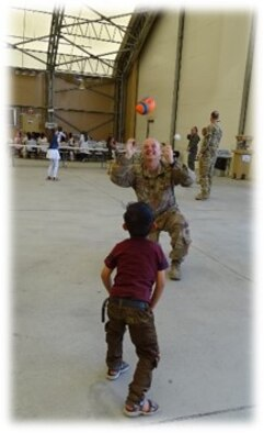 Chaplain Lt. Col. John W. Shipman plays catch with an Afghan child during an outreach event to the children of the Afghan Martyrs and a local Kabul orphanage to help build positive rapport with the local community on June 25, 2018.