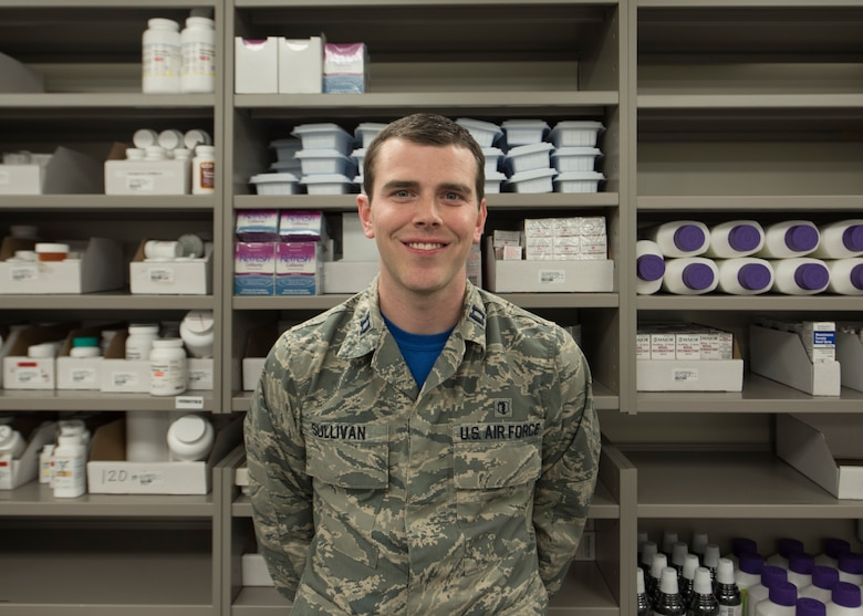 An Air Force officer smiles and stands in front of a shelving unit.