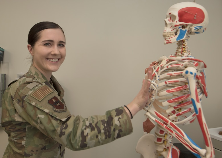An Air Force officer poses with a plastic skeleton.