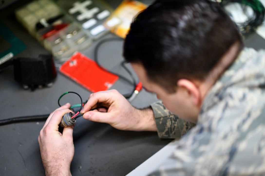 An Airman assigned to the 48th Component Maintenance Squadron's Electrical and Environmental section uses test leads on a throttle grip during an operations check at Royal Air Force Lakenheath, England, Jan. 23, 2019. The backshop developed a local standard to alleviate the need to send the component to a stateside facility for repair, saving $5,000 each time it's repaired. (U.S. Air Force photo by Senior Airman Malcolm Mayfield)