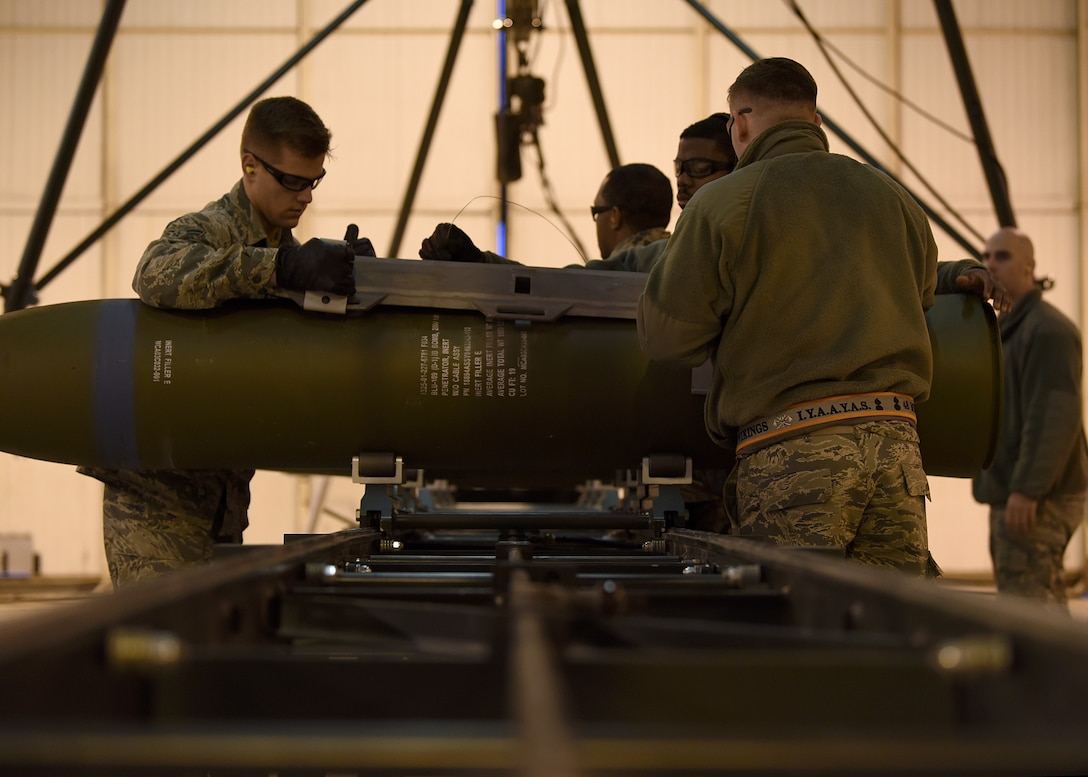 Airmen from the 48th Munitions Squadron attach the hardback assembly of an inert ordnance at Royal Air Force Lakenheath, England, Jan. 23, 2019. The Airmen were training for the Air Force Combat Operations Competition, an annual munitions-building competition designed to test participants on all of the aspects used by ammo personnel in wartime operations. (U.S. Air Force photo by Airman 1st Class Madeline Herzog)