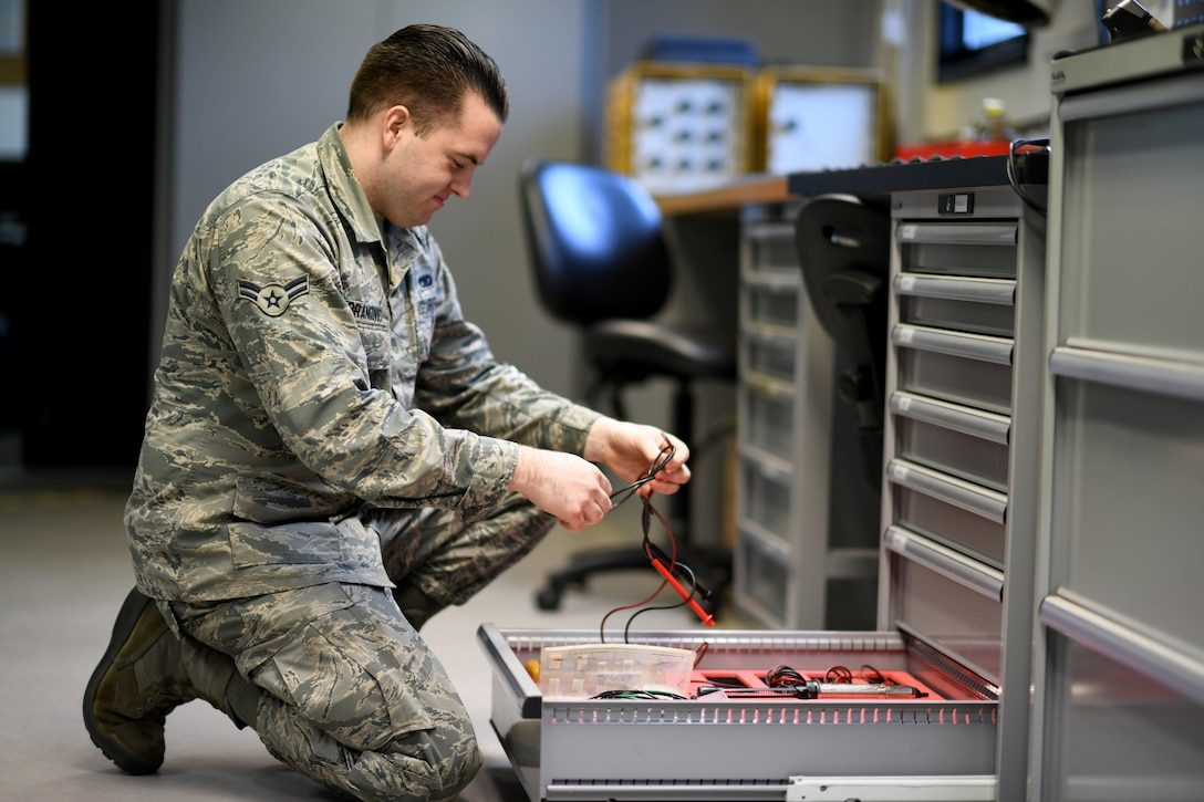 An Airman assigned to the 48th Component Maintenance Squadron's Electrical and Environmental section retrieves test leads for an operations check on equipment at Royal Air Force Lakenheath, England, Jan. 23, 2019. The test leads are used to send a surge of energy into a component testing its capabilities before it is returned to service. (U.S. Air Force photo by Senior Airman Malcolm Mayfield)