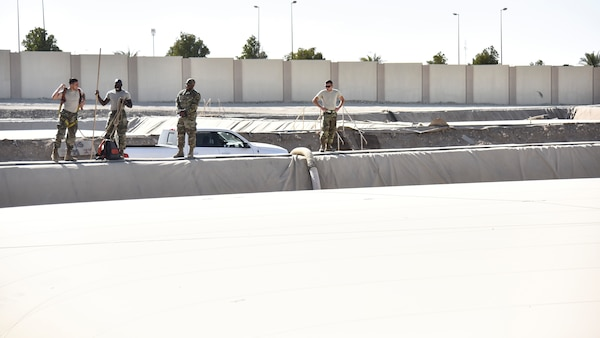 U.S. Airmen assigned to the 380th Expeditionary Logistics Readiness Squadron fuels flight, prepare to measure a fuel bladder at Al Dhafra Air Base, United Arab Emirates, Jan. 21, 2019. The fuel bladders have approximately the same thickness of a water bed liner, which is strong enough to hold 210,000 gallons of fuel. (U.S. Air Force photo by Senior Airman Mya M. Crosby)