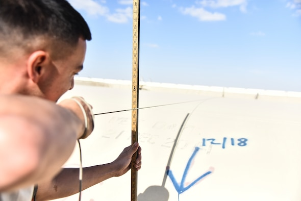 U.S. Air Force Senior Airman Tyler Ruano, 380th Expeditionary Logistics Readiness Squadron fuels operations technician, measures a fuel bladder at Al Dhafra Air Base, United Arab Emirates, Jan. 21, 2019. The fuel bladders have approximately the same thickness of a water bed liner, which is strong enough to hold 210,000 gallons of fuel. (U.S. Air Force photo by Senior Airman Mya M. Crosby)