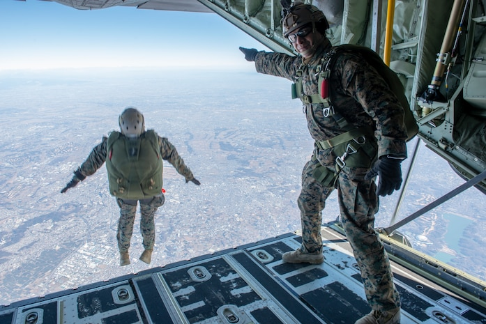A U.S. Marine directs the Marines out of the aircraft during freefall parachute training during Yokota Parachute Operations at Yokota Air Base, Japan, Jan. 17, 2019. The Yokota Parachute Operation is designed to allow the Marines the opportunity to refine their skills with static line and free-fall parachuting. The Marine is a jump master with 3rd Reconnaissance Battalion, 3rd Marine Division.