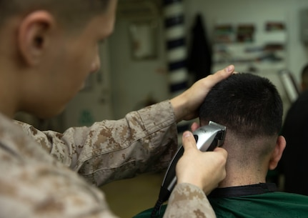 U.S. Marine Corps Cpl. Hector Gutierresseverino, a Marine with the 22nd Marine Expeditionary Unit, cuts hair in the barber shop aboard the Wasp-class amphibious assault ship USS Kearsarge, Jan. 21, 2019. The Marines and Sailors with the 22nd Marine Expeditionary Unit and Kearsarge Amphibious Ready Group are currently deployed to the U.S. 5th Fleet area of operations in support of naval operations to ensure maritime stability and security in the Central region, connecting the Mediterranean and the Pacific through the western Indian Ocean and three strategic choke points. (U.S. Marine Corps photo by Lance Cpl. Antonio Garcia)