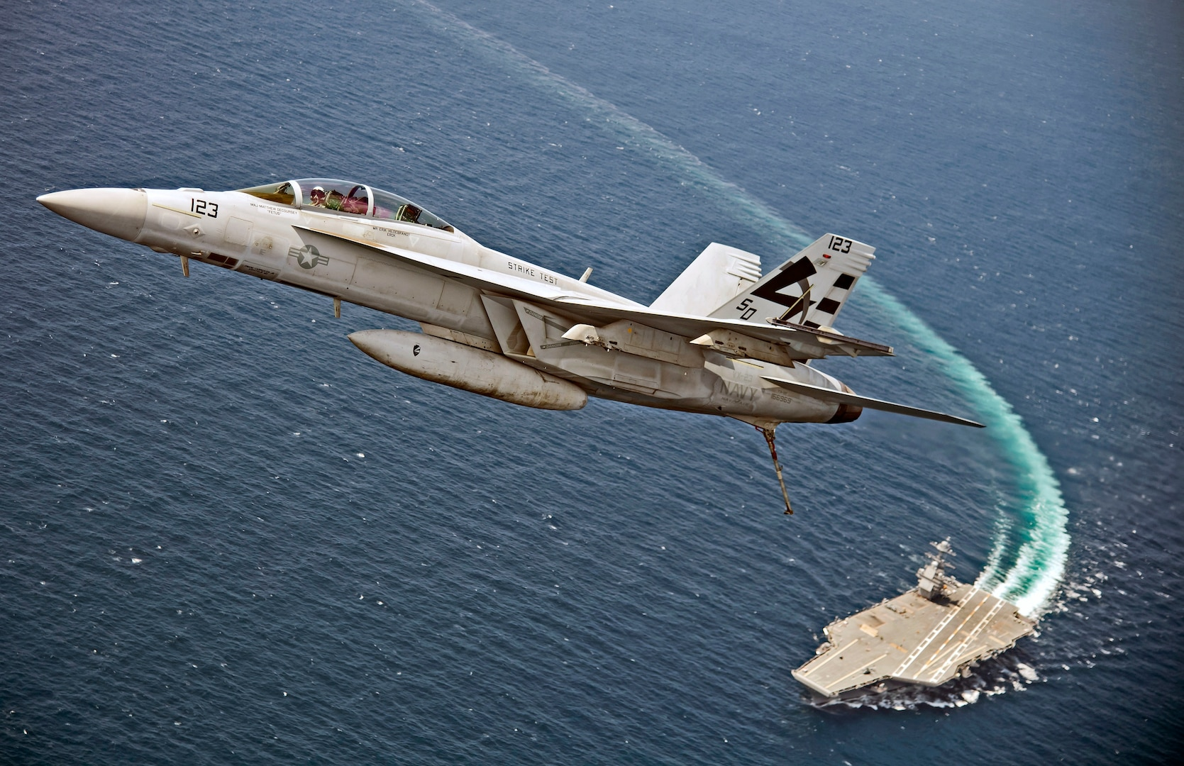 F/A-18F Super Hornet assigned to Air Test and Evaluation Squadron (VX) 23 flies over aircraft carrier USS Gerald R. Ford, July 28, 2017, in Atlantic Ocean (U.S. Navy/Erik Hildebrandt)