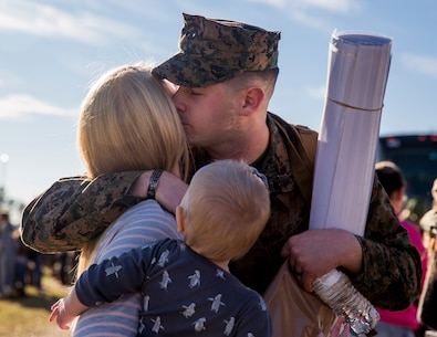 A U.S. Marine assigned to the 22nd Marine Expeditionary Unit hugs his family as he prepares to leave for an overseas deployment at Camp Lejeune, N.C. Dec. 18, 2018. The 22nd MEU will serve as a sea-based, expeditionary crisis response force, ready and able to conduct military operations on a moment's notice. (U.S. Marine Corps photo by Lance Cpl. Heather Atherton)