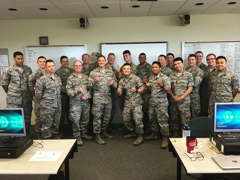 Shown here with is technical school class, Senior Airman Joe Chau, 718th Intelligence Squadron cyber systems operations technician, distinguish himself at technical school not only as a student, but also as a tutor. While there, he initiated an informal tutoring group which quickly grew from three classmates to more than 40 participants, promoted and endorsed by his tech school instructors.
