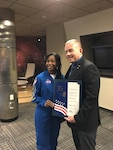 Female NASA astronaut presents a certificate to a male wearing a suit.