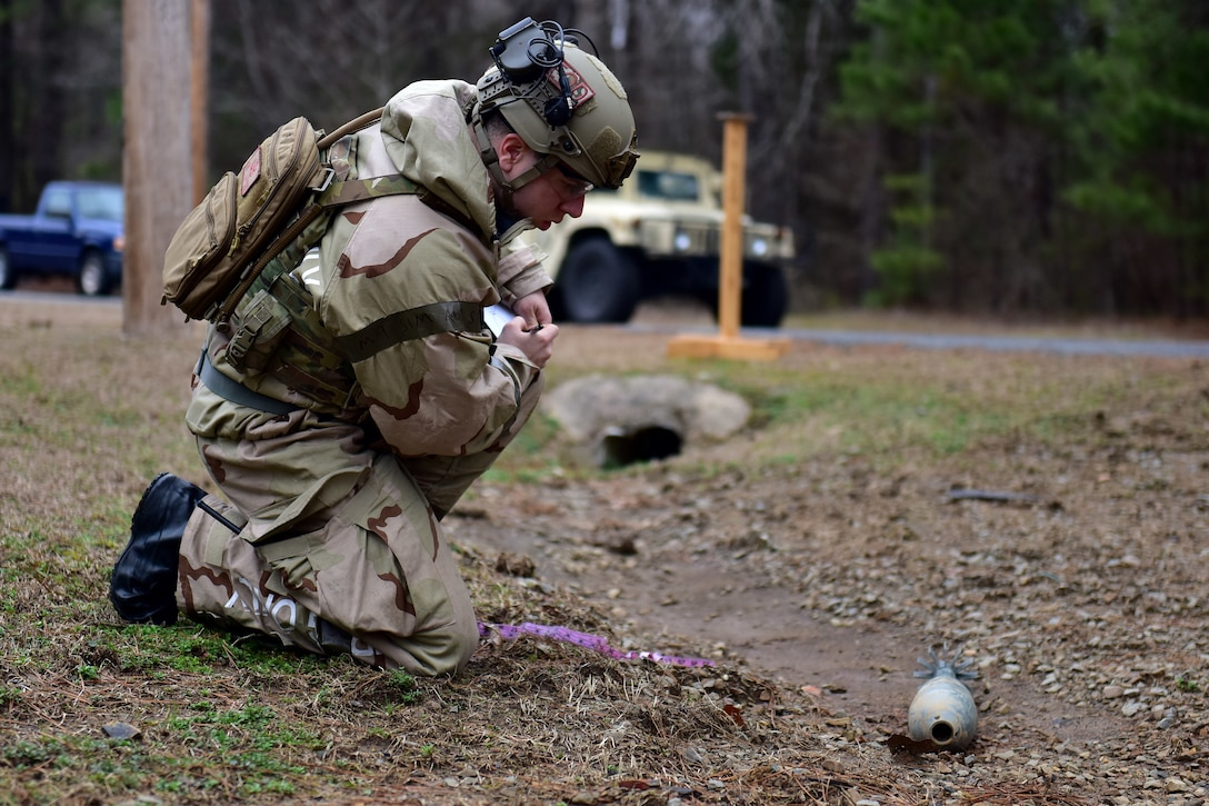 man kneeling next to plastic bomb taking notes of size and shape