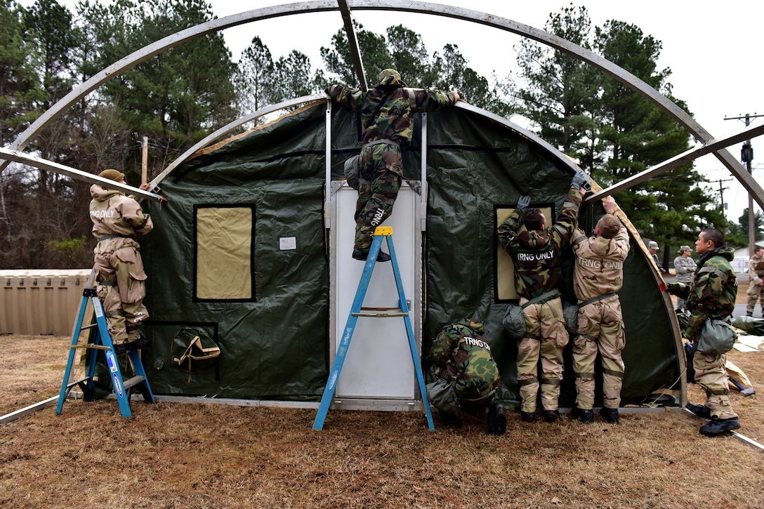 Many Airmen building temporary shelter pulling soft outer shell over metal frame