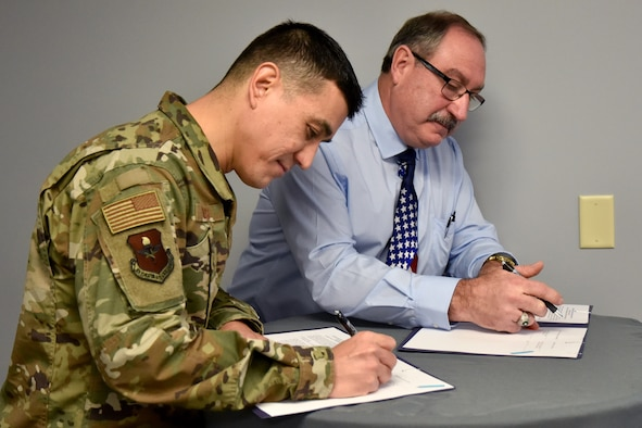 U.S. Air Force Col. Ricky Mills, 17th Training Wing commander, signs the Career Skills Program Memorandum of Understanding alongside Concho Valley Workforce Development Board Deputy Executive Director Mr. Randy LeCompte at the Business Resource Center on Jan. 25, 2019. This MOU helps transitioning service members develop workforce skills and potentially secure internships or employment within the local community. (U.S. Air Force photo by 2nd Lt. Matthew Stott/Released)