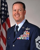 White man in Air Force Blues uniform standing in front of flag.